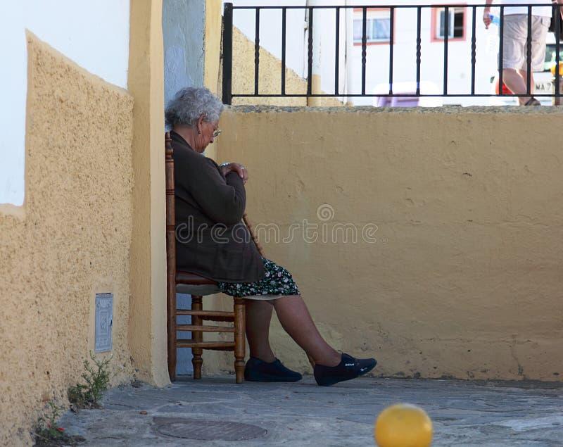 Ältere Dame, die auf dem Stuhl außerhalb ihres Hauses in Ronda stillsteht stockfotos