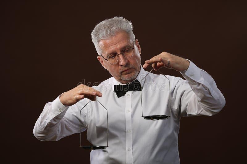 Älterer grauhaariger Mann 50s, im weißen Hemd, in den Gläsern und in der Fliege, die etwas auf Skalen mit kettlebells wiegt lizenzfreies stockfoto