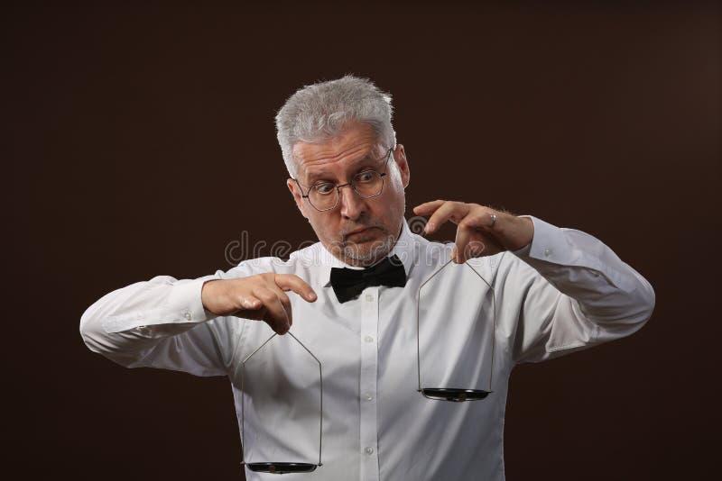 Älterer grauhaariger Mann 50s, im weißen Hemd, in den Gläsern und in der Fliege, die etwas auf Skalen mit kettlebells wiegt lizenzfreie stockbilder
