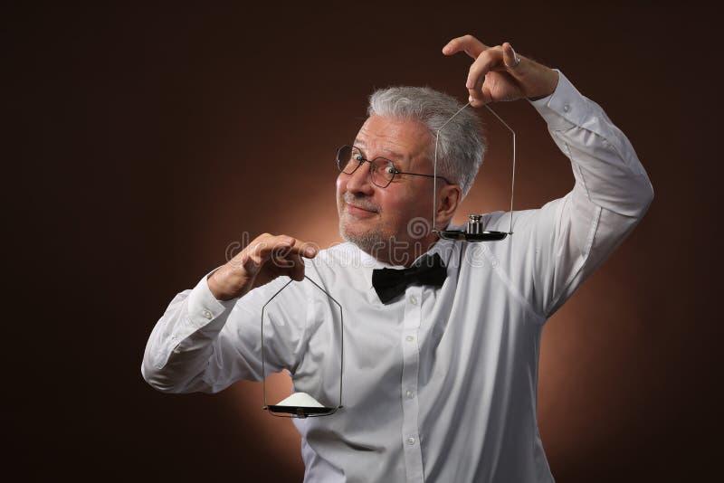 Älterer grauhaariger Mann 50s, im weißen Hemd, in den Gläsern und in der Fliege, die etwas auf Skalen mit kettlebells wiegt lizenzfreie stockfotos