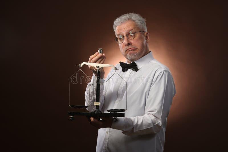 Älterer grauhaariger Mann 50s, im weißen Hemd, in den Gläsern und in der Fliege, die etwas auf Skalen mit kettlebells wiegt stockfotografie