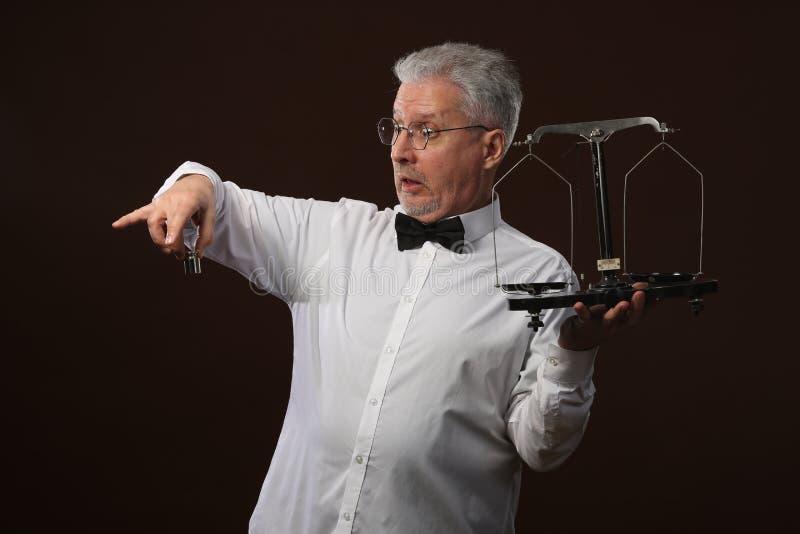 Älterer grauhaariger Mann 50s, im weißen Hemd, in den Gläsern und in der Fliege, die etwas auf Skalen mit kettlebells wiegt stockfotos