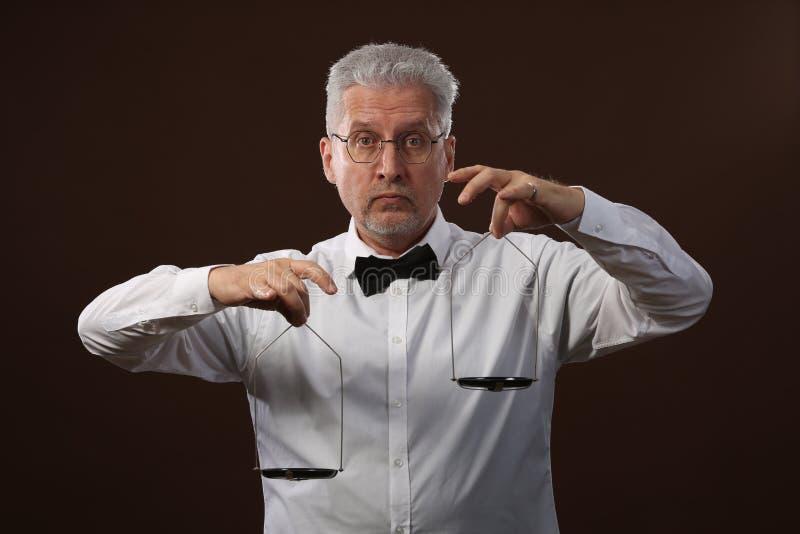 Älterer grauhaariger Mann 50s, im weißen Hemd, in den Gläsern und in der Fliege, die etwas auf Skalen mit kettlebells wiegt stockbild