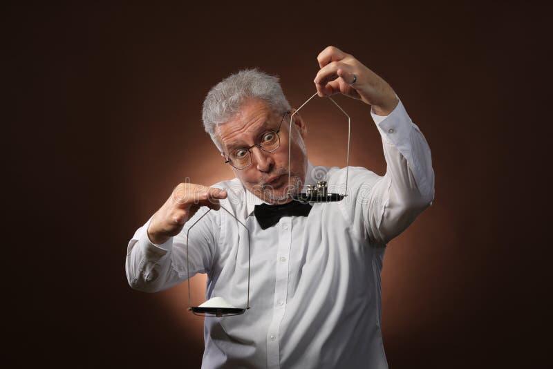Älterer grauhaariger Mann 50s, im weißen Hemd, in den Gläsern und in der Fliege, die etwas auf Skalen mit kettlebells wiegt stockfoto