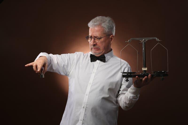 Älterer grauhaariger Mann 50s, im weißen Hemd, in den Gläsern und in der Fliege, die etwas auf Skalen mit kettlebells wiegt stockbilder