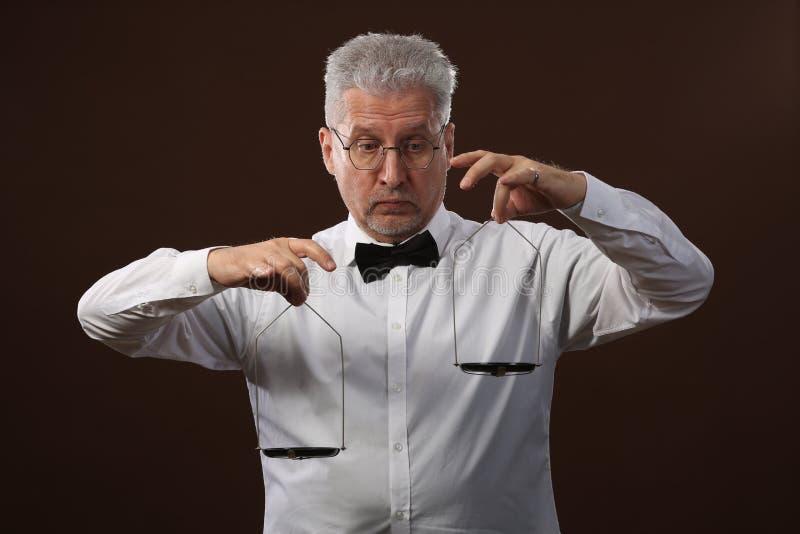 Älterer grauhaariger Mann 50s, im weißen Hemd, in den Gläsern und in der Fliege, die etwas auf Skalen mit kettlebells wiegt lizenzfreie stockfotografie