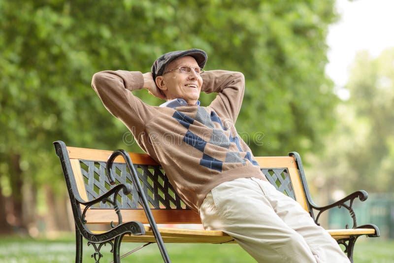Älterer Mann, der einen Tag auf einer Holzbank genießt lizenzfreies stockfoto