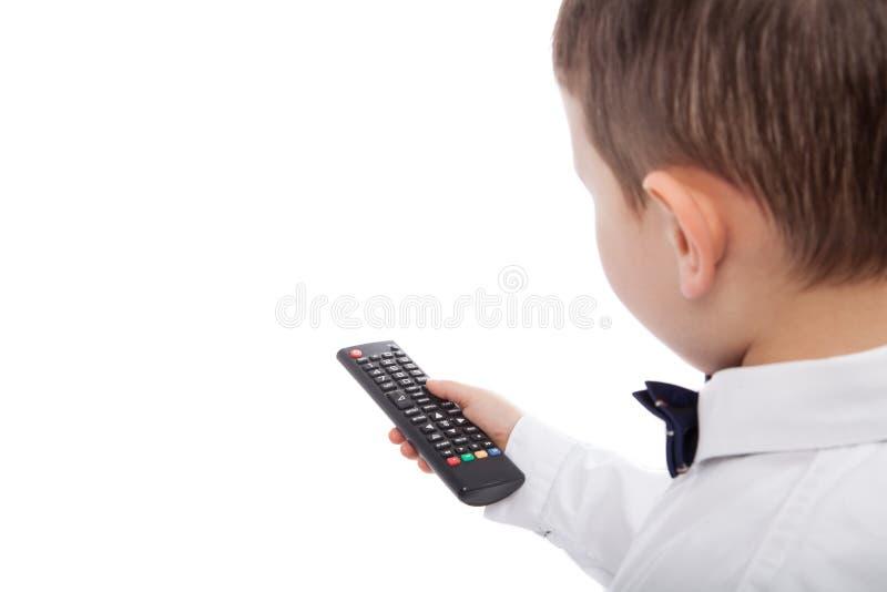 Ändernde Kanäle des kleinen Jungen im Fernsehen unter Verwendung der Fernbedienung, lokalisiert auf Weiß Leerer Raum stockbild