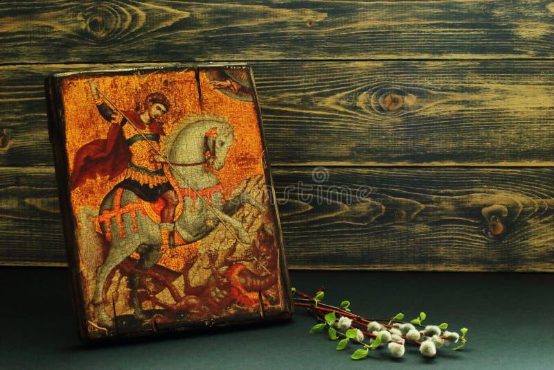 Ícone de St George os ramos vitoriosos da réplica e do salgueiro e do vidoeiro no fundo de madeira escuro Fé do †simbólico do c imagens de stock