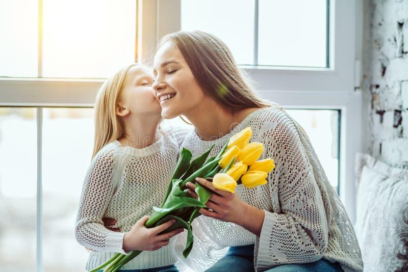 Ð- appy Muttertag! Kind beglückwünscht Mutter und gibt den Tulpen einen Blumenstrauß von Blumen lizenzfreie stockfotos