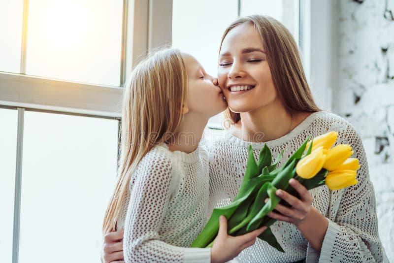 Ð  matek appy dzień! Mała dziewczynka daje mama kwiaty fotografia royalty free
