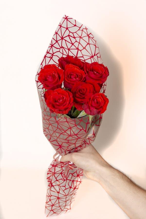 Übergeben Sie das Halten des Blumenstraußes der roten Rosen über weißem Hintergrund lizenzfreie stockfotos