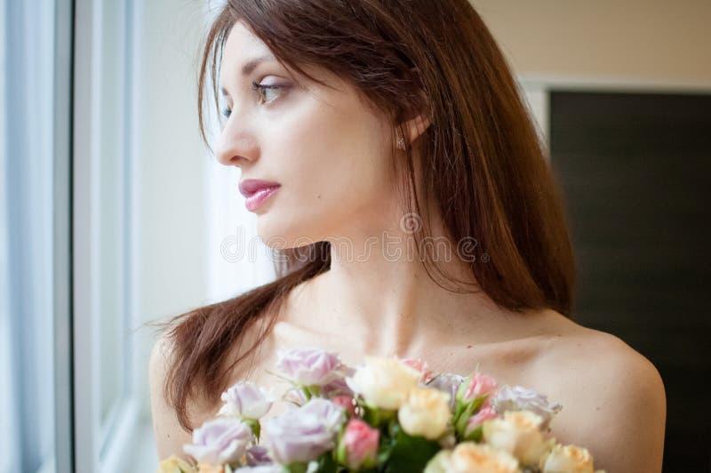 Überraschende fashinable Frau mit den sinnlichen Lippen, die einen Blumenstrauß der Blumen halten und durch das Fenster früh in s lizenzfreie stockbilder
