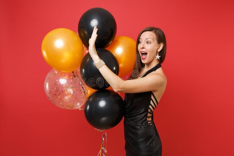 Überraschte junge Frau im schwarzen Kleid feiernd, wellenartig bewegende Hand für die Grußhaltenen Luftballone lokalisiert auf ro lizenzfreie stockfotografie