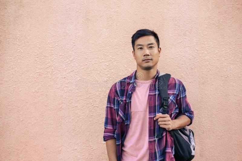 Überzeugte junge asiatische Mannstellung außerhalb des Tragens eines Rucksacks lizenzfreie stockfotos