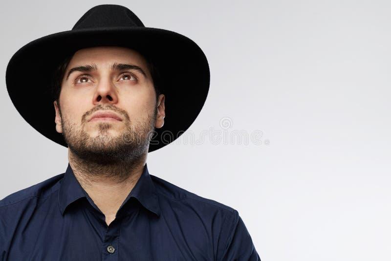 Überzeugter hübscher hispanischer Mann, der den schwarzen Hut schaut oben lokalisiert auf weißem Hintergrund trägt stockbild