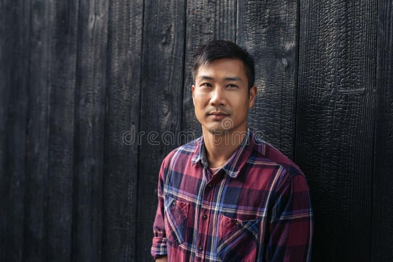 Überzeugter junger asiatischer Mann, der draußen eine dunkle Wand bereitsteht lizenzfreie stockfotos