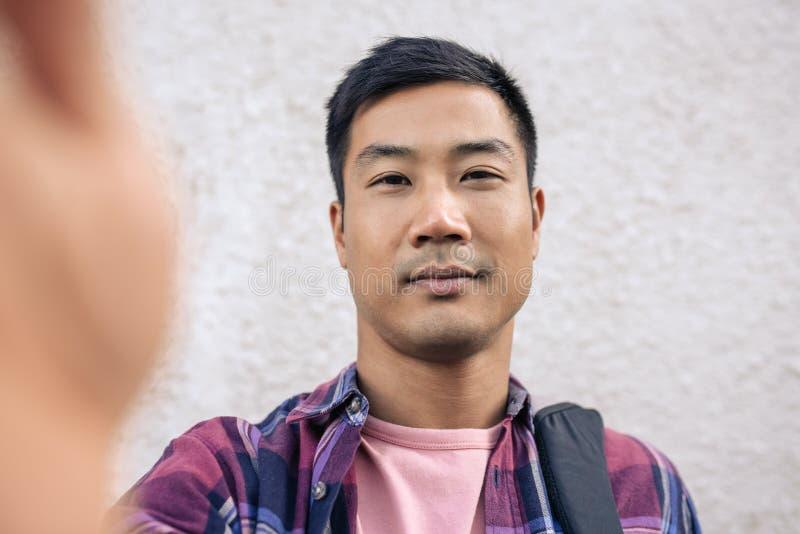 Überzeugter junger asiatischer Mann, der eine selfie Außenseite nimmt stockbilder