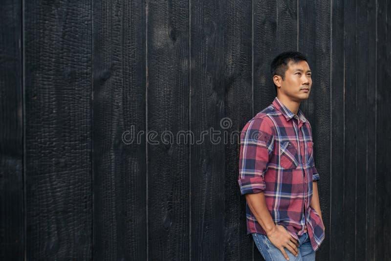 Überzeugter junger asiatischer Mann, der sich draußen an einer dunklen Wand lehnt lizenzfreies stockfoto