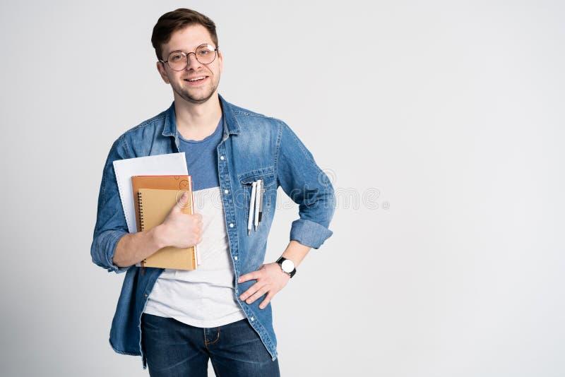 Überzeugter Kursteilnehmer Studioporträt des hübschen jungen Mannes, der Bücher hält Lokalisiert auf Weiß stockfotografie