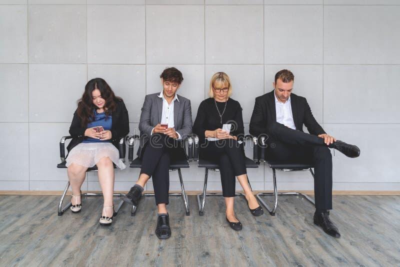 不同种族的工作申请人繁忙使用膝上型计算机和智能手机为吸收的谈话做准备,不同的求职者在队列坐 库存照片