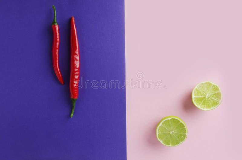不同的口味的组合的概念在烹调的 在紫罗兰色背景的辣椒在桃红色一的纸和石灰 顶视图射击机智 免版税库存图片