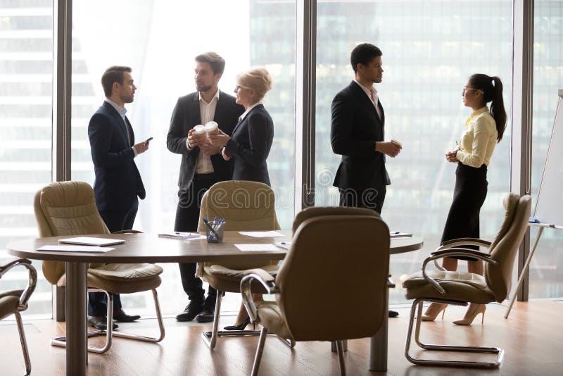 不同的多种族雇员身分分别地谈话在工休 库存图片