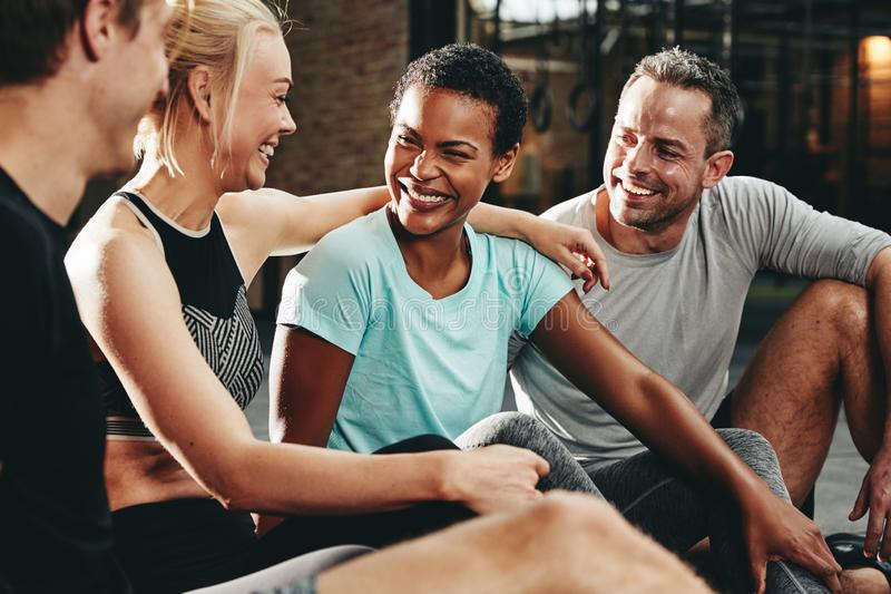 不同的小组微笑的朋友谈话在健身房地板上 免版税库存图片