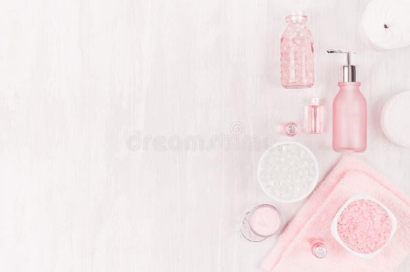 不同的化妆品和辅助部件在桃红色和银色颜色在柔光白色木背景,拷贝空间,顶视图 免版税库存图片