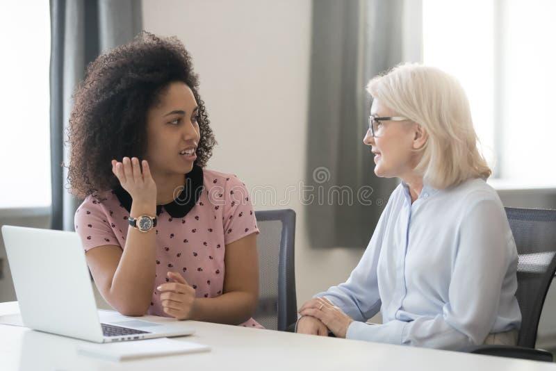 不同的老和年轻女性同事谈话在工作 库存图片