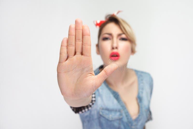 不要来到我 画象偶然蓝色牛仔布衬衣的严肃的美丽的年轻女人有红色头饰带身分的和看 免版税库存图片