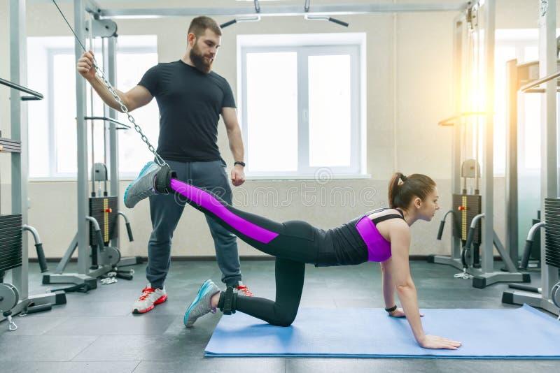 不随意运动技术,运动疗法,健康生活方式 做与个人辅导员使用的年轻女人修复锻炼 库存图片