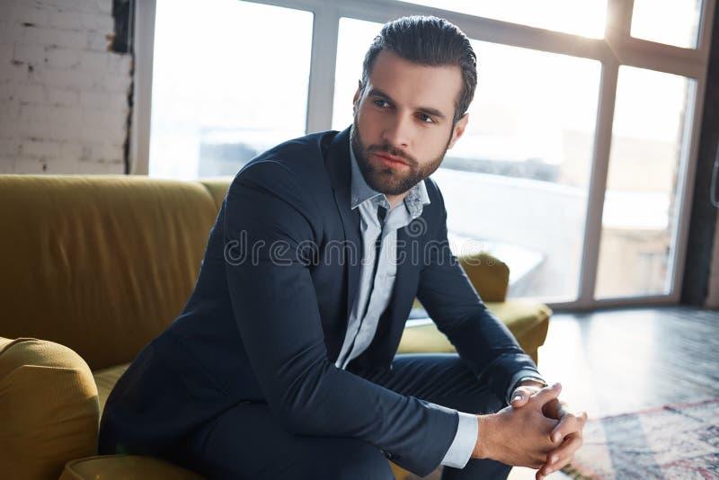 丢失在企业想法 周道的英俊的年轻商人考虑事务,当坐沙发时 免版税库存图片