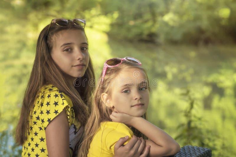 两个女孩外面坐一好日子 妹在夏天森林里 免版税库存照片