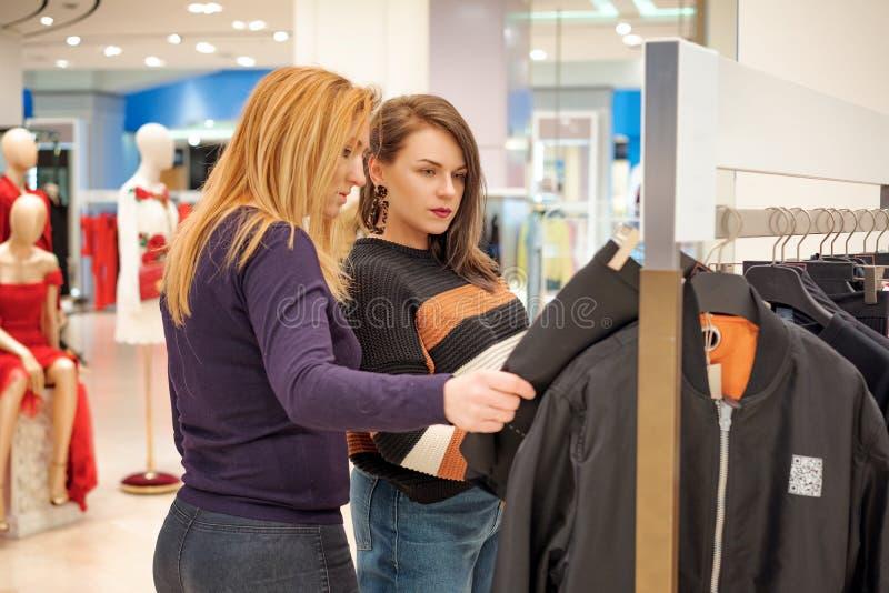 两个女孩在商店去购物,选择衣裳 免版税库存照片