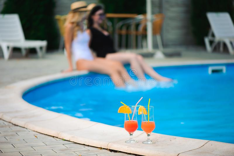两个女孩松弛近的水在度假 免版税库存图片