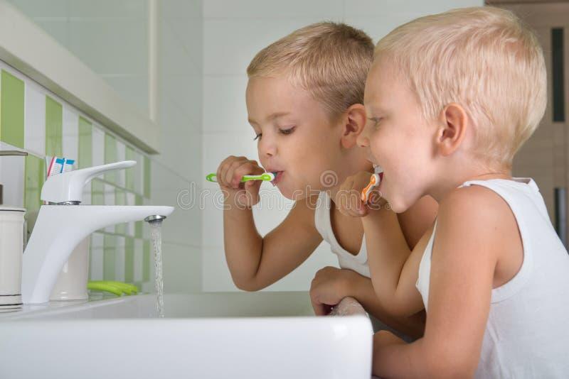 两个兄弟在卫生间里刷我的牙 一新的天的初期 免版税库存照片