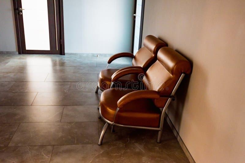 两个棕色皮椅在大厅或等候室里 免版税库存照片
