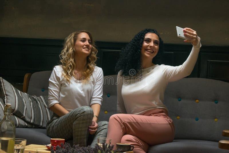 两个最佳的女朋友采取在咖啡馆的selfie 库存图片