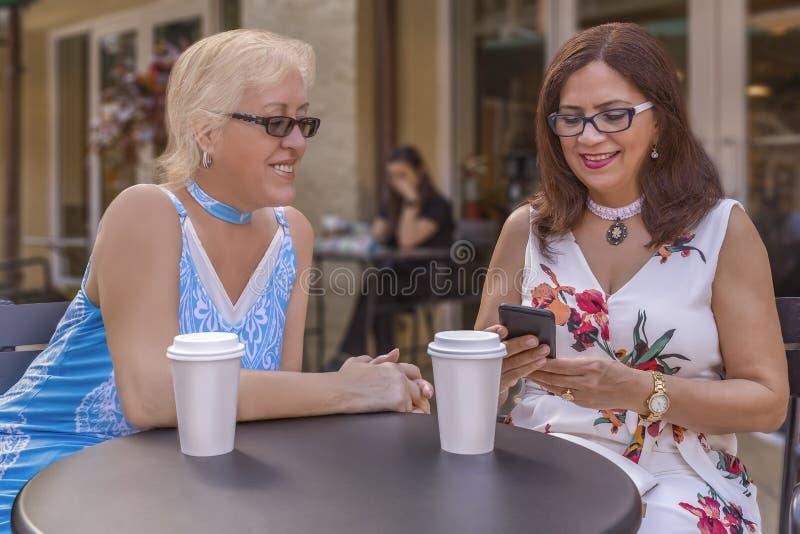 两个成熟朋友享用咖啡户外,当看智能手机时 库存图片