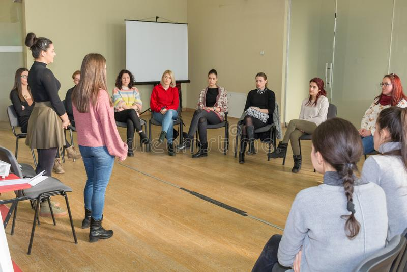 两个老师和小组年轻学生有小组讨论在大教室和在圈子坐椅子 免版税库存图片