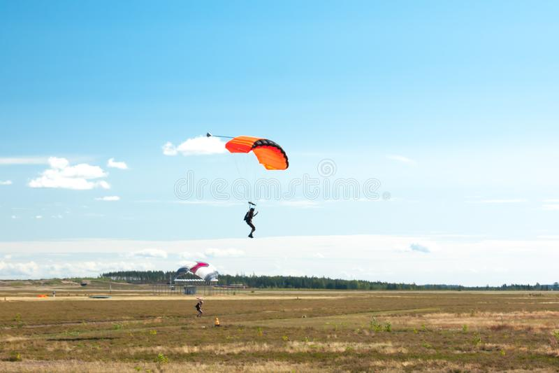 两个飞将军在五颜六色的降伞登陆到机场 图库摄影