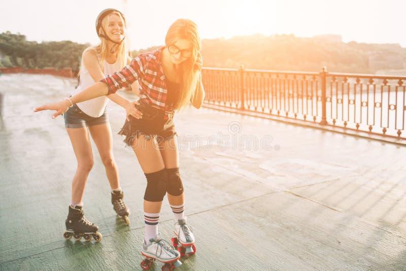 两亭亭玉立和性感的少妇和溜冰鞋 一位女性有轴向冰鞋,并且其他有方形字体冰鞋 女孩 免版税库存照片