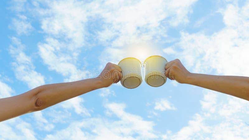 两只亚洲妇女手使热的咖啡杯叮当响室外早晨 朋友喜欢一起喝咖啡 清楚的天空背景 免版税库存图片