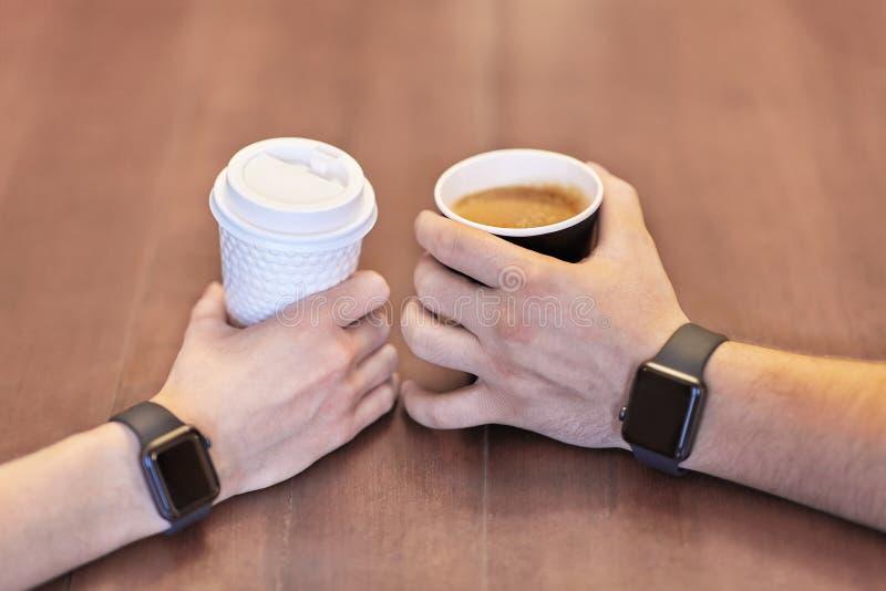 两只手、男性和女性,两个与相等的电子手表,拿着咖啡,白色和黑,在木桌上 免版税库存图片
