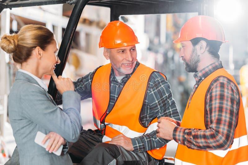 两名使用铲车机器的工作者和审查员 库存图片
