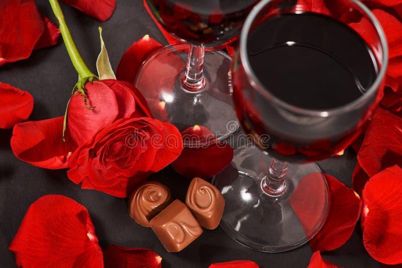 两杯酒、玫瑰、瓣和巧克力在黑背景 免版税库存照片