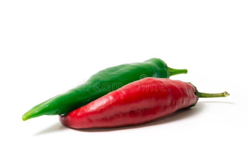 两红色和在白色背景的绿色辣椒 食物的香料 明亮的水多的颜色 库存照片