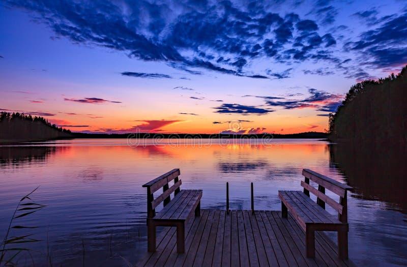 两长木凳或椅子在面对湖的木船坞在日落在芬兰 图库摄影