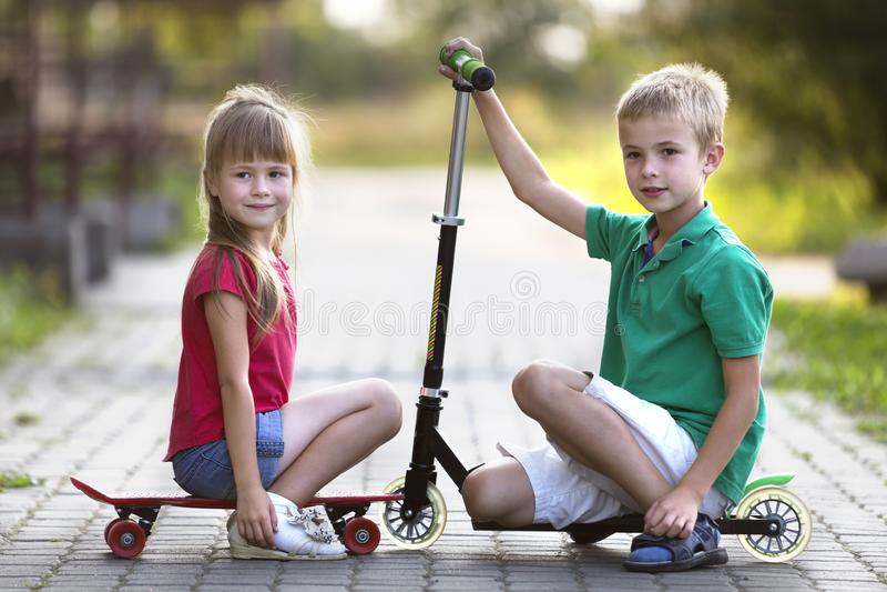 两逗人喜爱的愉快的滑稽的微笑的小孩子,兄弟和姐妹,摆在为照相机,帅哥有滑行车的和相当长 图库摄影
